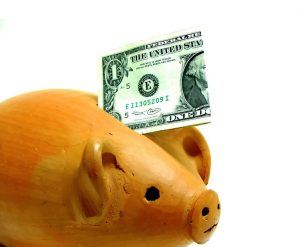 dollar-bill-going-into-wooden-piggy-bank